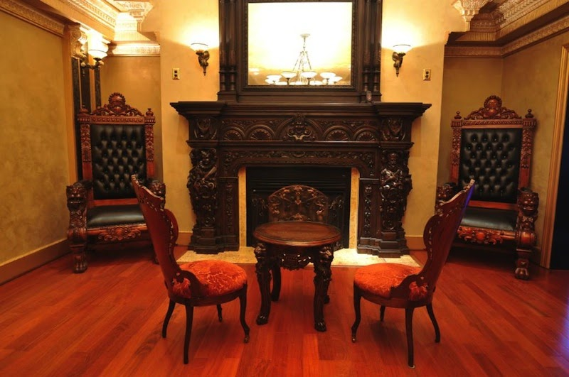 A Different Mansion Here With Old World Castle Like Chairs Beside The  Mantle And A Victorian Style Table And Chairs Facing The Mantel.