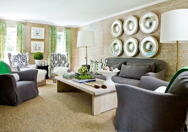 Living room with six rounds mirror arranged on a sea grass walls, reclaimed wood coffee table, grey sofas, gray ikat armchairs and a woven sea grass sisal rug