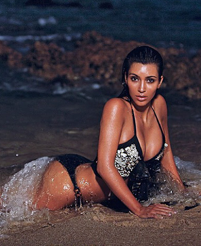 Kim Kardashian wearing a two piece bikini and posing for cameras