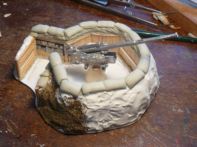 Final layer of spackle, beginning to add basing material, showing off a larger field gun that also fits nicely in the emplacement.