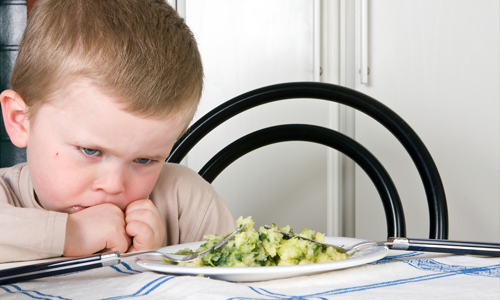 A frowning, picky eater, at the dinner table.