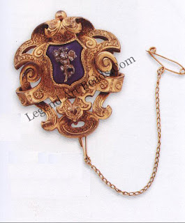 A wonderfully detailed mid-Victorian brooch, e.187o, of chased 15-carat gold. The blue enamel central shield underlies a silver, rose-cut diamond flower.