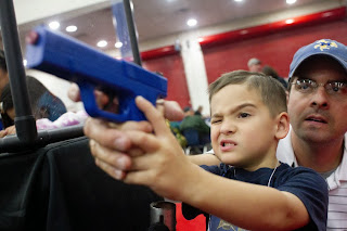 Young child using a lethal firearm with the encouragement of his father.
