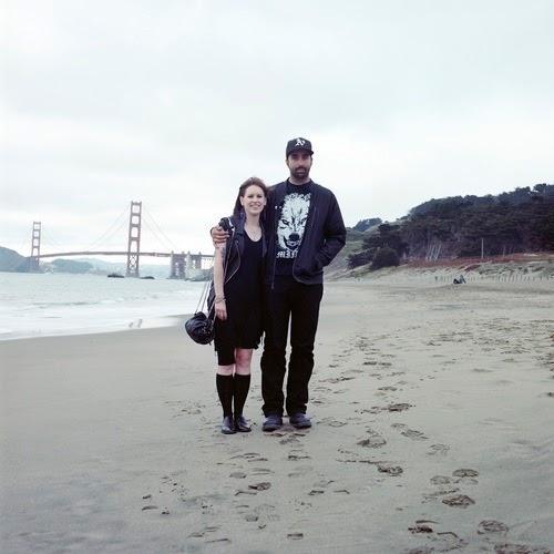 Nesta foto o casal está em uma praia, com uma ponte ao fundo. Eles vestem roupas pretas, a mulher está de saia, e o rapaz de jaqueta de couro e boné.