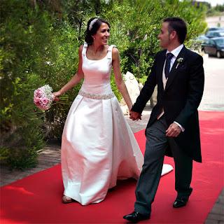 Los novios se miran enamorados caminando por la alfombra roja. Qué guapos están los dos!!
