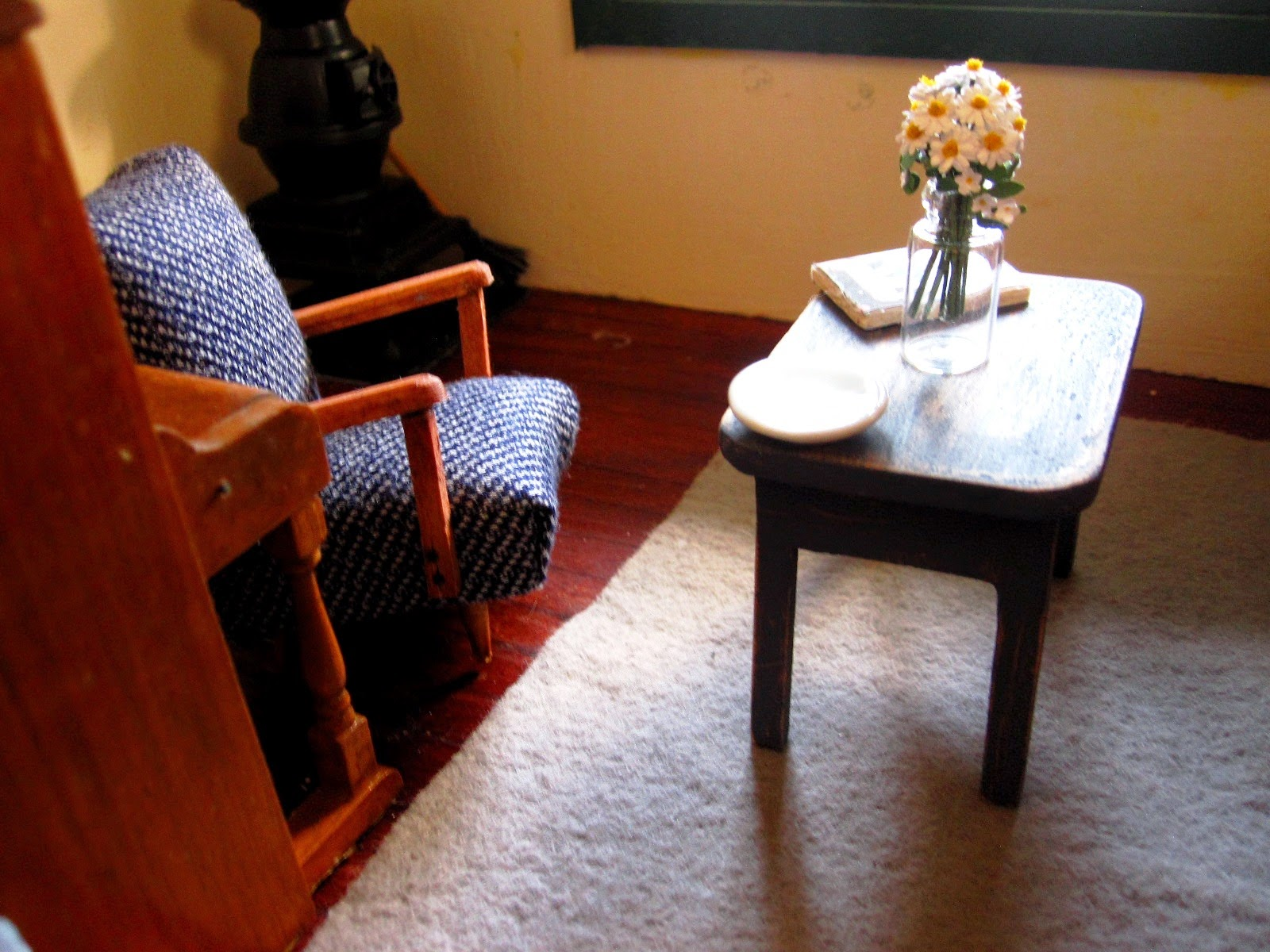 Dolls house miniature sitting area with a 1950s-style reading chair and a small shabby coffee table with a vase of daisies on it.