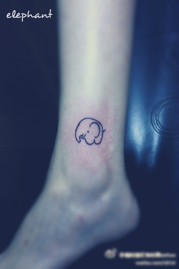 a cute little comic style elephant tattoo on the leg