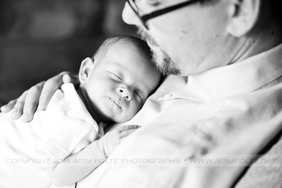 black and white photo of newborn sleeping on daddy's chest