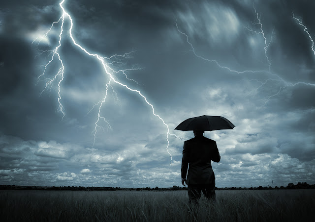 silhouette of man with umbrella standing in lightning storm