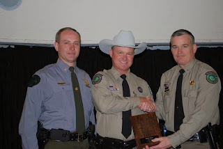 Teeler (right) congratulates the 2013 Officer of the Year for the Association of Midwest Fish and Game Law Enforcement.