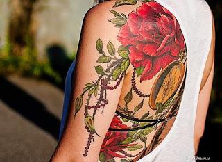Tatuagem nas costa de ramos de rosas e relógio