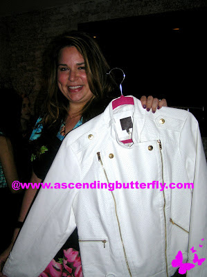 Aimee Cheshire CEO of Madison Plus holds up a White Jacket from MYNT 1792 at Madison Plus Select Press Preview Event at Alison Eighteen in New York City