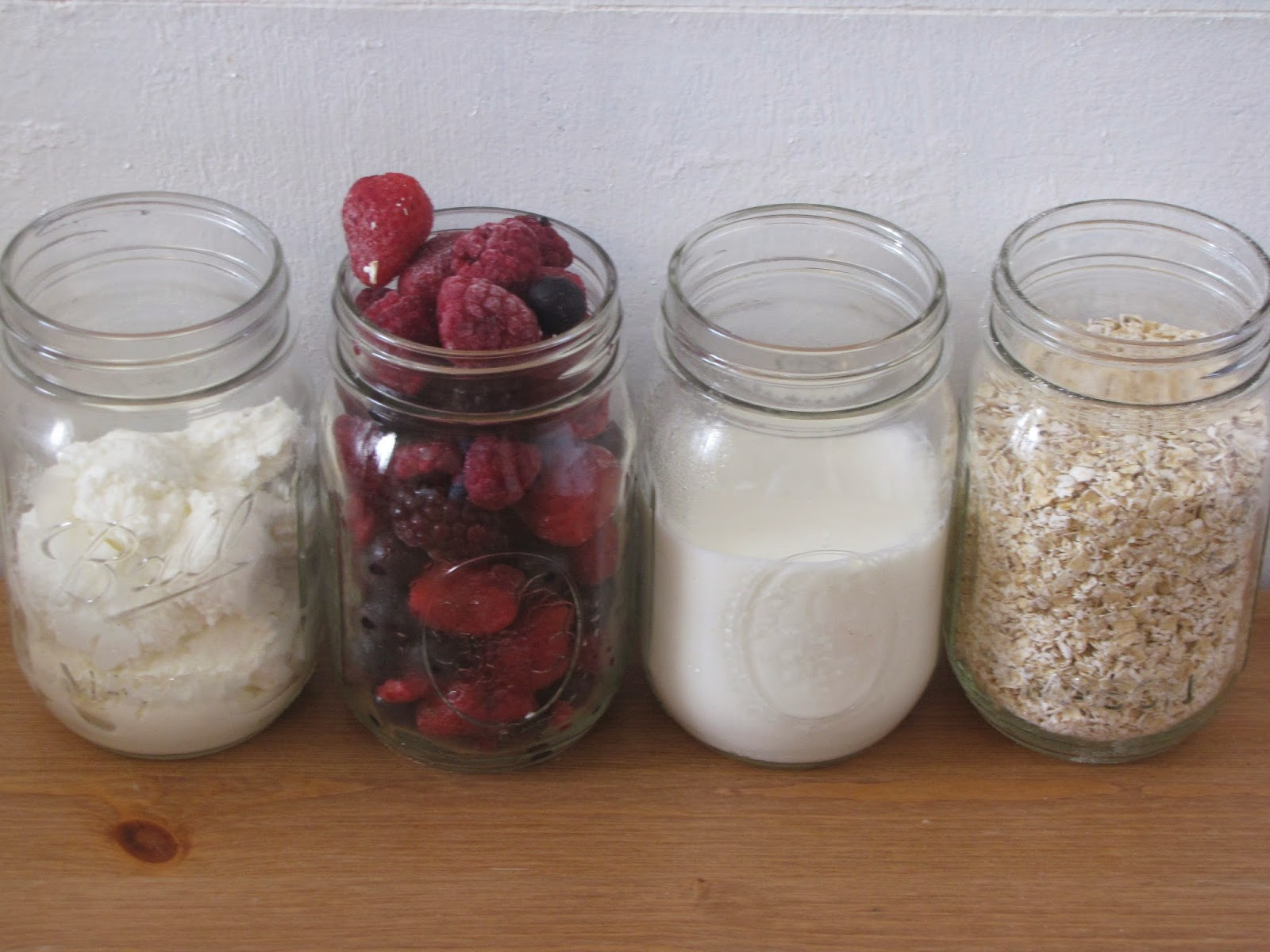 Ricotta, frozen berries, milk and oats measured out for pancakes in mason jars