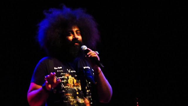 Reggie Watts performing on stage at the Fox Theater during a Boulder concert.