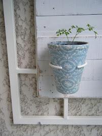 Um vaso decorado com tecido encaixado numa argola
