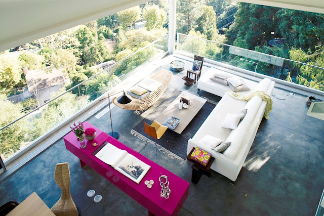 living room with concrete floors, modern sectional sofa, a hot pink credenza and disappearing glass walls that expose a gorgeous hillside view