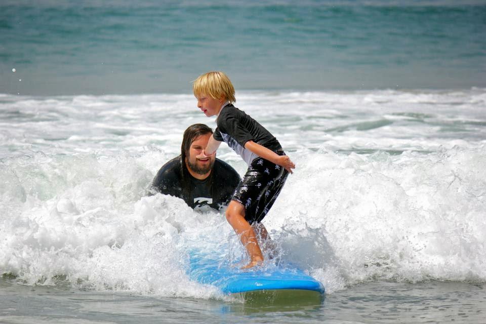 Boy camper surfing at Zuma Beach in Malibu with the assistance of Aloha Beach Camp surf instructor Matthew Duda.Matt