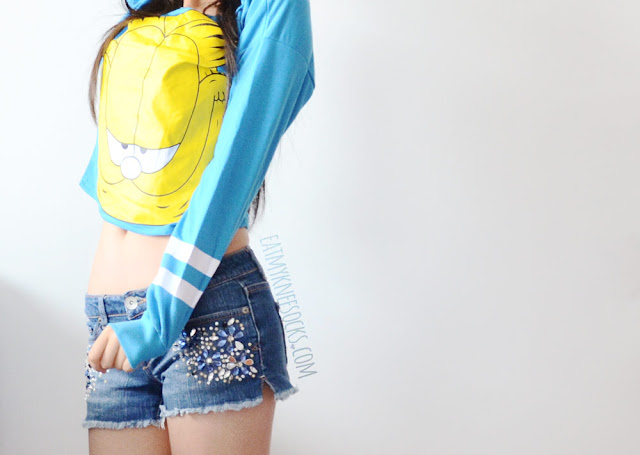 A cute, casual, Asian streetwear-inspired outfit featuring CrossWalk's printed Garfield long-sleeve sweatshirt and rhinestone-embellished denim shorts.