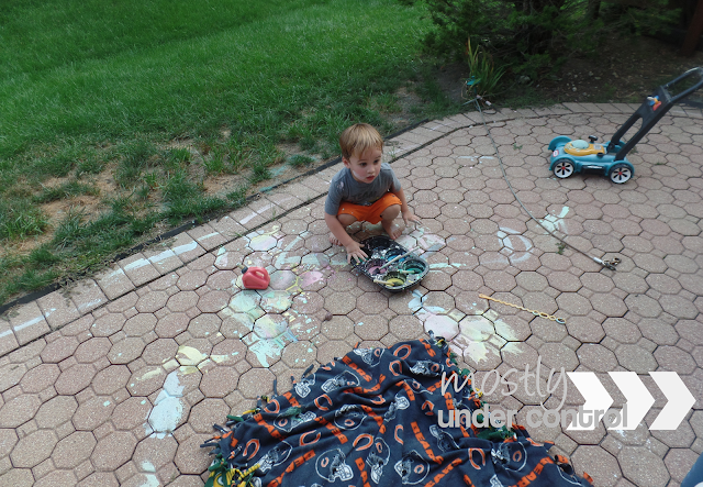 overhead image of a boy toddler playing with chalk paint on the patio