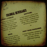 This is a photograph of a vintage menu showing 'Colonial Beverages' at the America Eats Tavern.