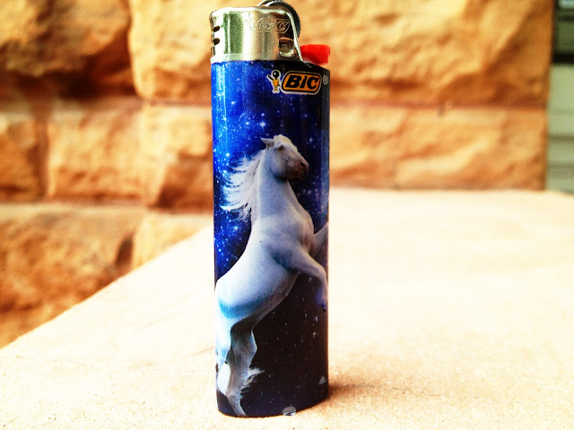 A white horse standing on it's back legs on a Bic lighter.