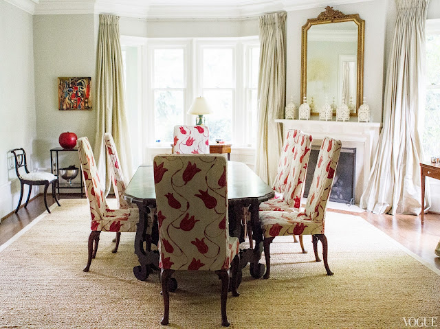 Dining room in Vogue.com contributor Sophie Young's childhood home with Queen Anne chairs upholstered in red and white floral print, a fireplace with white Moroccan lanterns on the mantel and a large gilded mirror