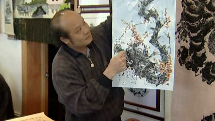 Xu Huang with one of his paintings
