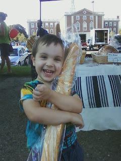 toddler hugging loaf of french bread