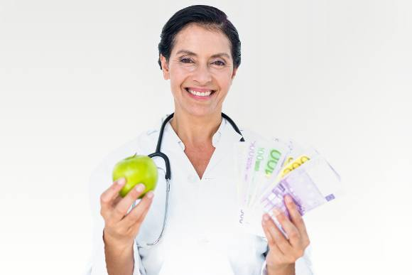 smiling doctor holding apple and money