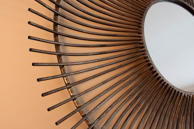 close-up of metal sunburst mirror in lamplight