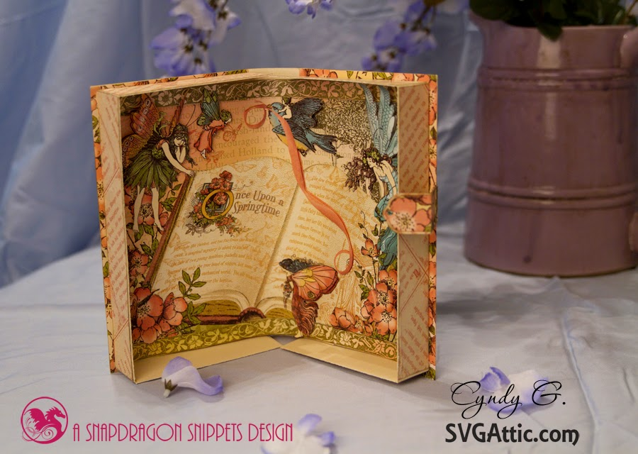 Open book with a scene of fairies and beautiful flowers around a book in the forest