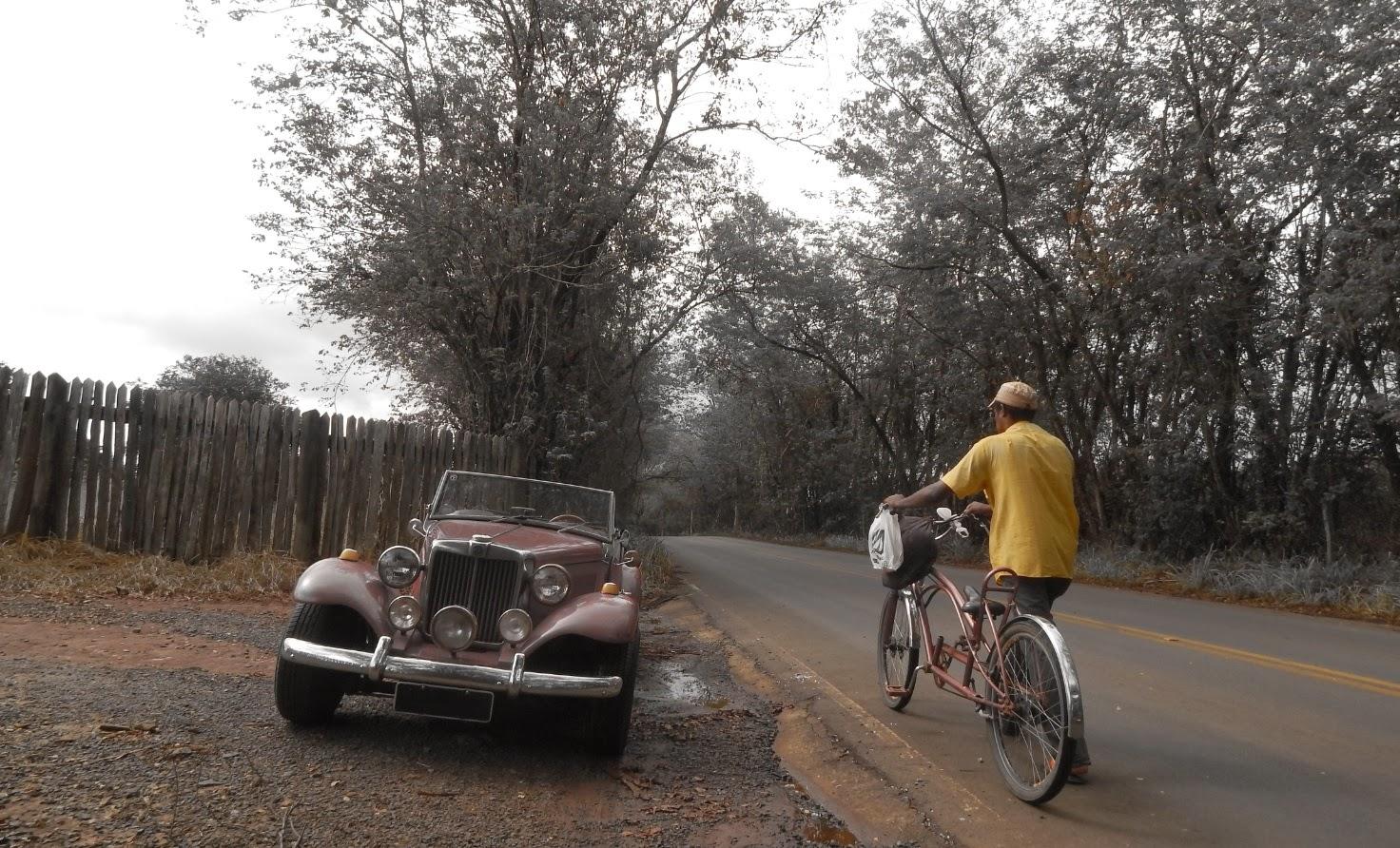 Estradas vicinais não contam com acostamentos. Por isso as porteiras dos sítios funcionam como respiros - um local seguro para estacionar. Mas o condutor da bicicleta customizada não tem alternativa para chegar em casa