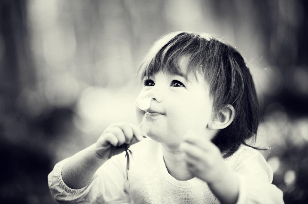 Barn luktar på vitsippa