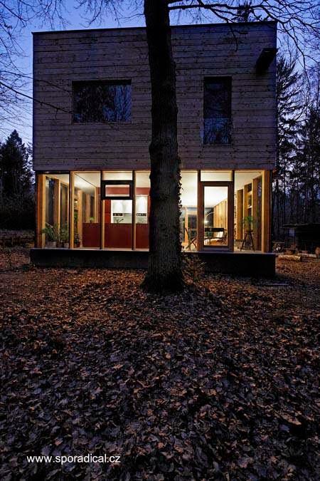 Vista nocturna de casa de madera contemporánea entre árboles