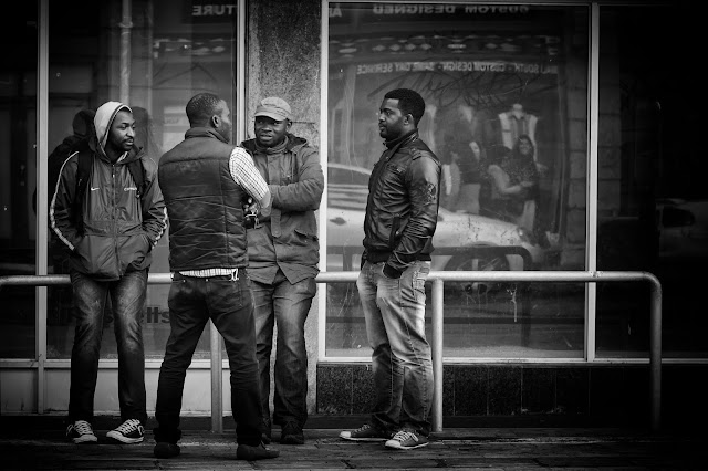 Four men stand in relaxed conversation.