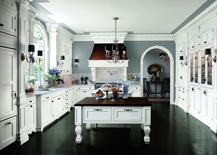 dark wood floors and blue walls give this white kitchen an extra pop
