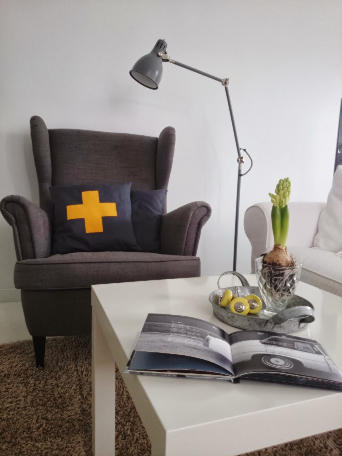 Szary fotel z ikei, szara poduszka z żółtym plusem, szara lampka z ikea, biały stolik, hiacynt na stoliku