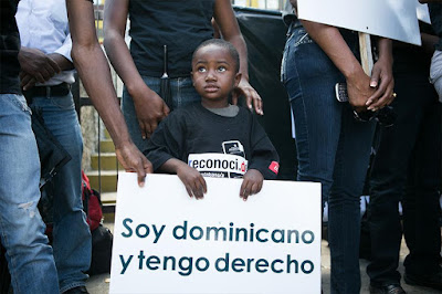 "A Dominican child, whose mother was affected by recent changes in Dominican  nationality law, holds up a sign (""I am Dominican and I have rights"") during a  vigil of the Reconoci.do movement in front of the Central Electoral Board in  Santo Domingo, March 11, 2013 (Fran Afonso)"