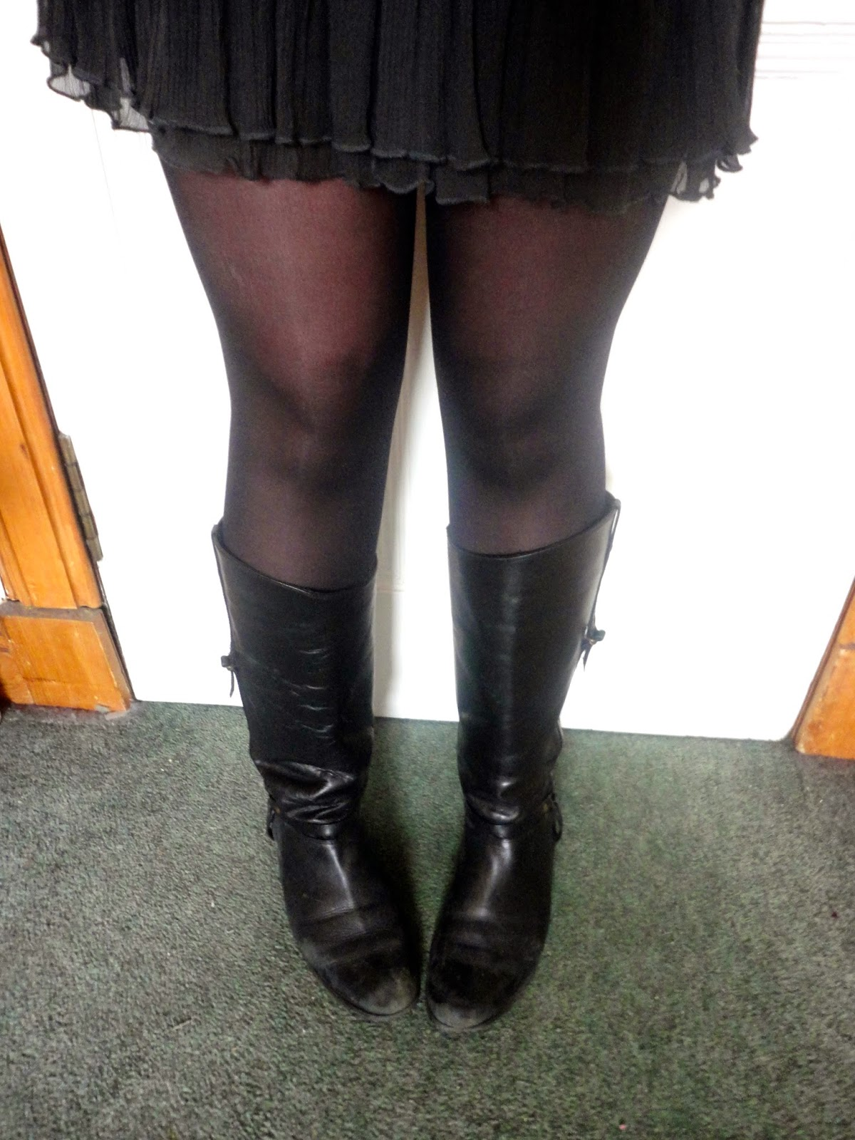 Outfit details of tall black leather riding boots, with black tights and lacy grey dress hem