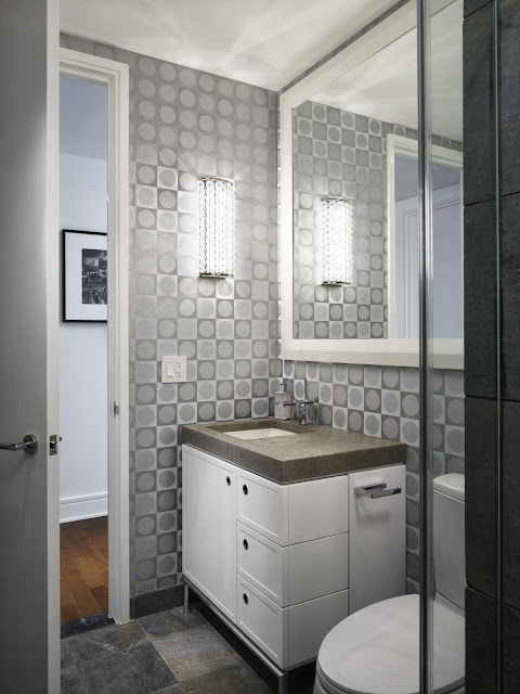 patterned tiles, minimalist vanity and wide mirror to open up this bathroom space