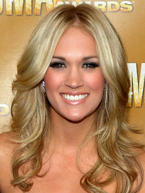 A strong center-part and curled layers give Carrie Underwood a sophisticated and glamorous look.