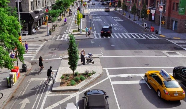 New York one-way, multi-lane, street at a four-way intersection, with protected bike lane in the far left