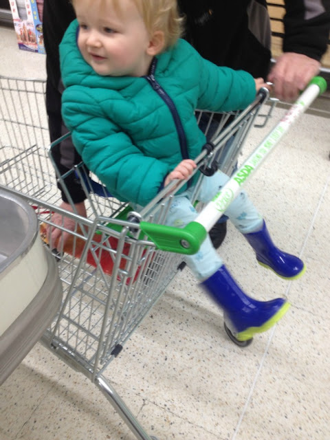 toddler in shopping trolley wearing his wonderful wellies