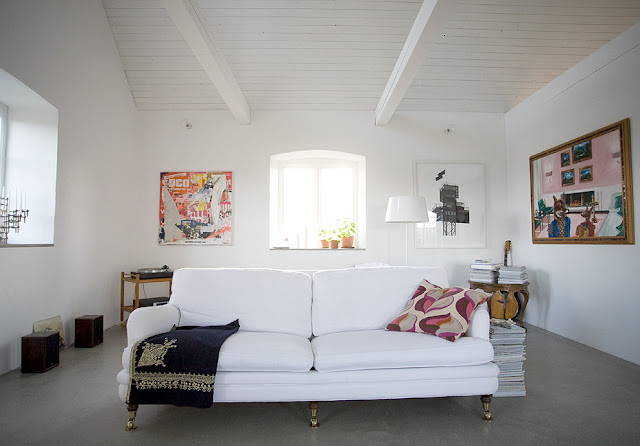 minimalist decor living room gray cement floors beam ceiling white sofa wood tapered legs brass casters