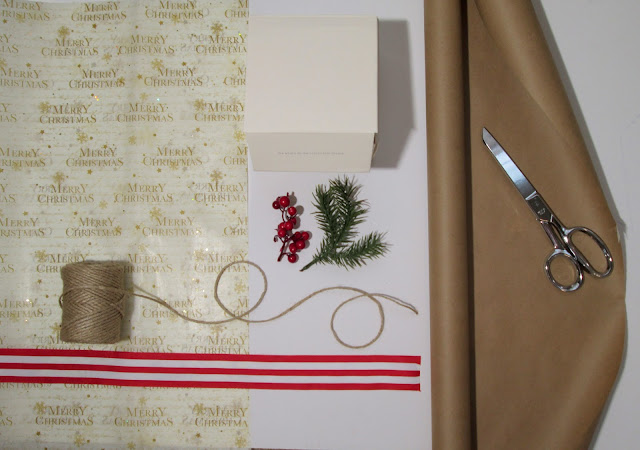 Gift wrap theme with tree sprigs, striped ribbon, berries, twine, gift box and brown paper