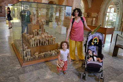 An image of K and the girls in front of an exhibit in the Chania Archaeological Museum with many bulls from a rural sanctuary