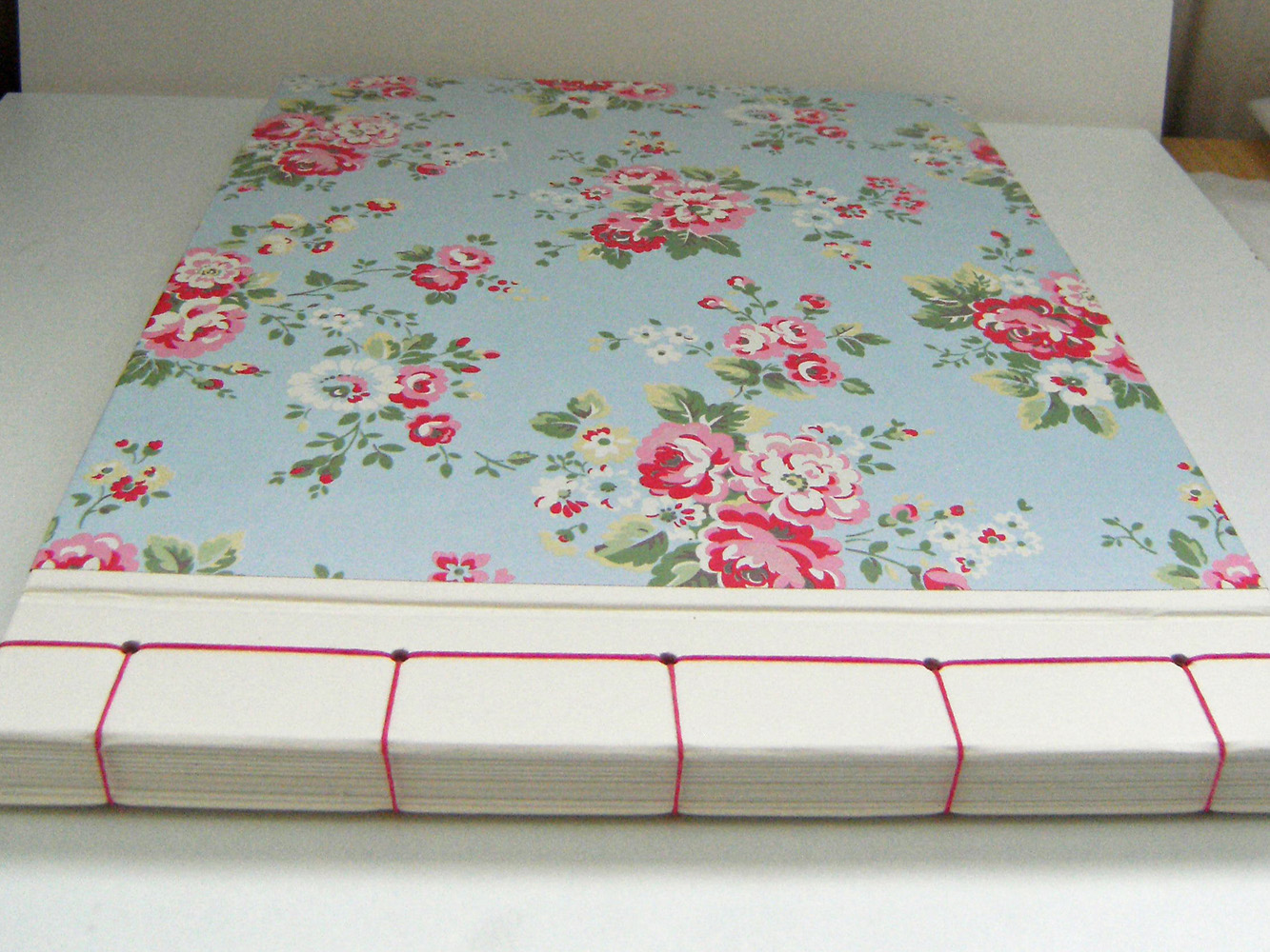 the book measures 1175 x 874 approx a4 size it has a japanese style stab stitch binding in bright pink waxed linen thread the bound edge and inside