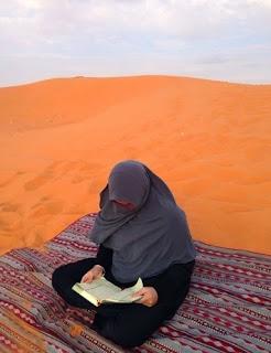 wanita muslimah baca quran di gurun pasir
