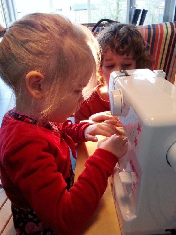 Daar gaat peuter op de kindernaaimachine