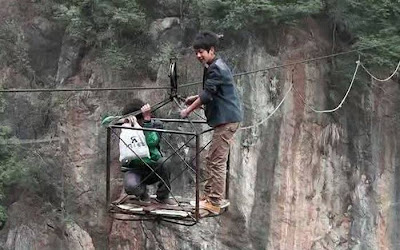 To get to school each day children living in a mountainous village in China have to cross a valley hundreds of metres deep on a rickety, homemade cable car. Villagers who live in Decun village in southwest China's Guizhou Province used to have to make the journey on foot, which took five hours, but in 2002 local man Hui Defang built a simple cableway.Picture: Quirky China News / Rex Features
